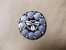 Applikation mit Kaurimuscheln und Münzen